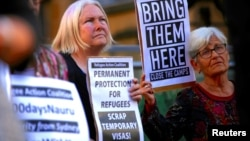 FILE - Refugee advocates hold placards and banners during a protest in central Sydney, Australia, Oct. 5, 2016, calling for the closure of the Australian detention centers in Nauru and Manus Island.