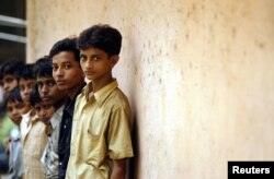 FILE - Indian child labourers rescued from different factories stand in a queue as a policeman (not pictured) records their names at a police station in Bombay in this June 1, 2005.