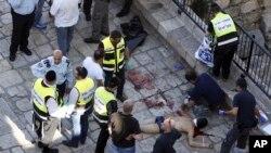 Socorristas y policías israelíes rodean el cuerpo de un palestino que presuntamente atacó a dos policías en Jerusalén este viernes.