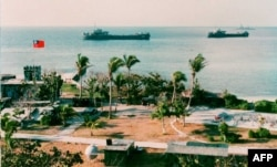 FILE - This photo released by the Military Information Agency in Taiwan shows two Taiwanese warships docking near the shore of Taiping Island, the largest of the disputed Spratly Island chain, with the Taiping military base in the foreground.