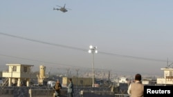 Afghan security forces keep watch as a NATO helicopter flies over at the site of an attack in Jalalabad December 2, 2012. Suicide attackers detonated bombs and fired rockets outside a major U.S. base in Afghanistan on Sunday, killing five people in a braz