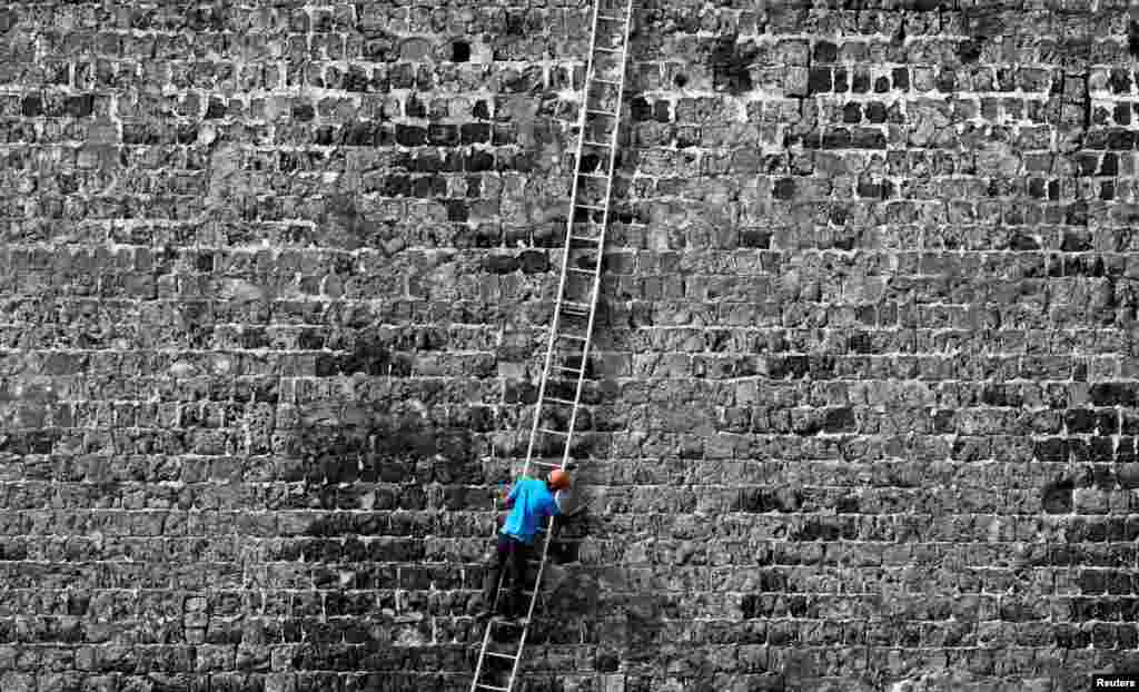A worker cleans a wall at the Jaffna Fort, a fort built by the Portuguese in 1618, in Jaffna, Sri Lanka.