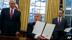 President Donald Trump shows an executive order to withdraw the U.S. from the 12-nation Trans-Pacific Partnership trade pact Jan. 23, 2017. With him are Vice President Pence (L) and Chief of Staff Reince Priebus. (AP Photo/Evan Vucci)