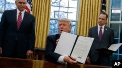 Predsednik Donald Tramp, u prisustvu potpredsednika Majka Pensa i šefa kabineta Rajnsa Pribusa, pokazuje uredbu o povlačenju SAD iz TPP-a