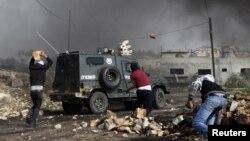 Des palestiniens jettent des pierres sur un véhicule de la police frontalière israélienne dans le village de Kfar Kadum, en Cisjordanie, près de Naplouse, le 25 janvier 2013.