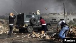 Des Palestiniens jettent des pierres sur un véhicule de la police israélienne près de la colonie juive de Kdumim, dans le village de Kfar Kadum, 25 janvier 2013.