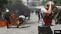 Para demonstran melemparkan batu dan bom-bom molotov ke arah petugas keamanan di Athena (28/6).