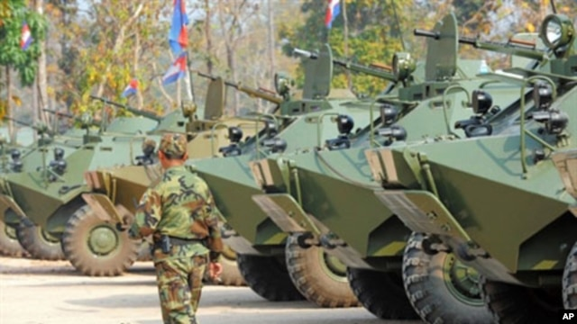 A Cambodian soldier walks past armored vehicles during the National Assembly members' visit to troops in a military base near the Preah Vhear temple in Preah Vihear province, some 500 kilometers northwest of Phnom Penh, February 9, 2011