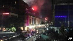 被疏散的雇员和客人沿街站立,从马尼拉云顶世界酒店中冒出滚滚浓烟(2017年6月2日)