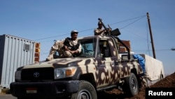 Army soldiers guard a checkpoint outside Amran city, north of Sanaa, amid tension with Shiite Houthi militants on April 13, 2014.
