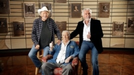 Bobby Bare, left, Jack Clement, center, and Kenny Rogers, right, pose for photographers in the Country Music Hall of Fame in Nashville, Tennessee, April 10, 2013.