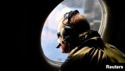 Một thành viên trong đoàn tìm kiếm chiếc máy bay mất tích MH370 quan sát qua cửa kính một chiếc máy bay đang bay trên Ấn Độ Dương