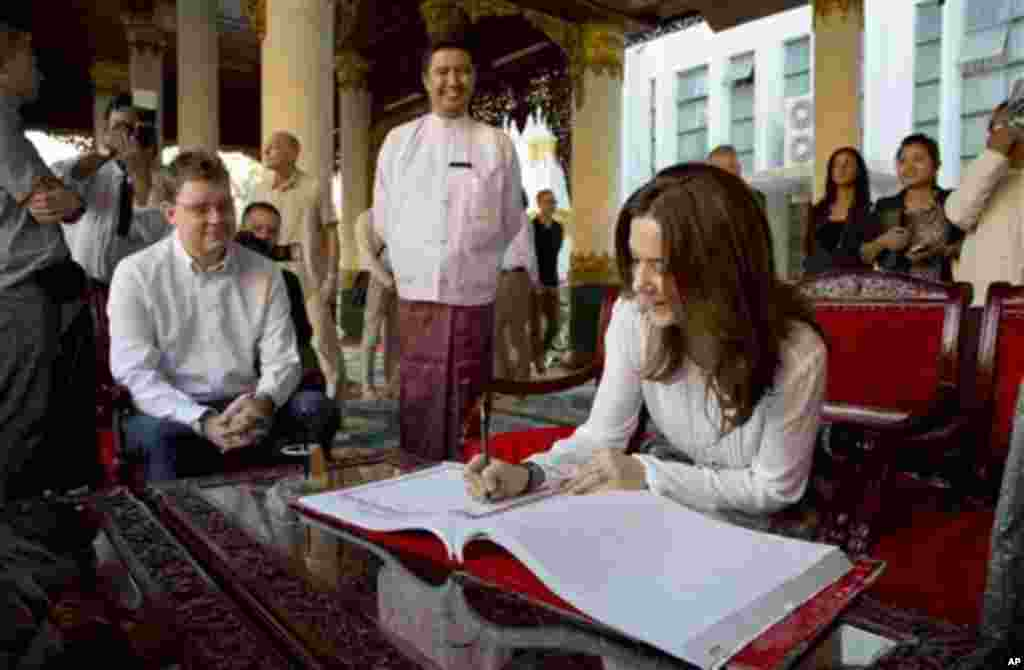 Denmark's Crown Princess Mary signs the visitors' book next to Danish Minister for Development Cooperation Rasmus Helveg Petersen, left, during a visit to Shwedagon Pagoda, considered as Myanmar's holiest Buddhist shrine, in Yangon Saturday, Jan. 11, 2014