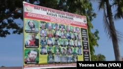 Baliho daftar DPO teroris Poso di depan Mapolres Poso. (VOA/Yoanes Litha)