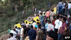 Indian people helping to rescue injured after a private school bus falls into a deep gorge in Nurpur, Kangra district, April 9, 2018.