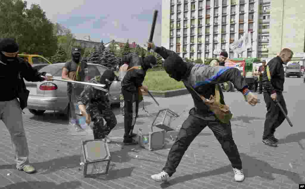 Pro-Russian militants smash ballot boxes in front of the seized regional administration building in Donetsk, Ukraine, May 25, 2014.