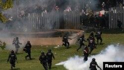 Polisi anti huru-hara Thailand berupaya mengejar para demonstran anti pemerintah yang berupaya masuk ke stadion pemuda Thai-Japan di pusat kota Bangkok mengacaukan persiapan pemilu (26/12).