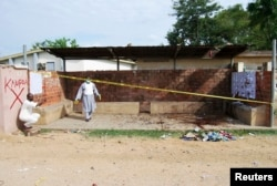 FILE - Security officers inspect the site where a female suicide bomber blew herself up at the campus of the Kano State Polytechnic, in Kano, northern Nigeria, July 30, 2014.