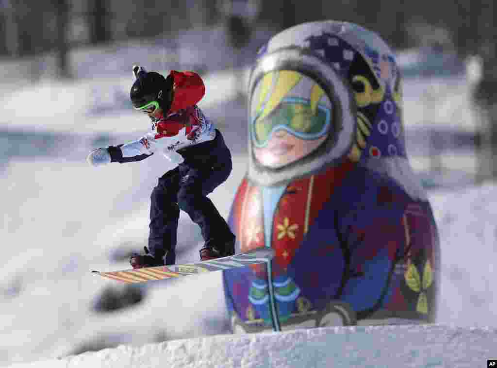 A competitor takes a jump past a giant matryoshka doll during a Snowboard Slopestyle training session at the Rosa Khutor Extreme Park, prior to the 2014 Winter Olympics, Feb. 4, 2014.