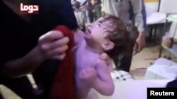 FILE - A child cries as its face is wiped following an alleged chemical weapons attack in Douma, Syria, in this still image from video obtained by Reuters, April 8, 2018.