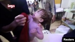 A child cries following an alleged chemical weapons attack, in what is said to be Douma, Syria, in this still image from video obtained by Reuters, April 8, 2018.