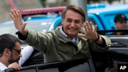 Jair Bolsonaro waves after voting in the presidential runoff election in Rio de Janeiro, Brazil, Sunday, Oct. 28, 2018. (AP Photo/Silvia izquierdo)