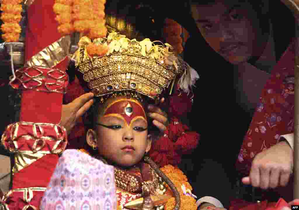 A Nepali child revered as a living goddess, or Kumari, is carried in a chariot during a procession on the main day of the Indra Jatra festival at Basantapur Durbar Square in Kathmandu.