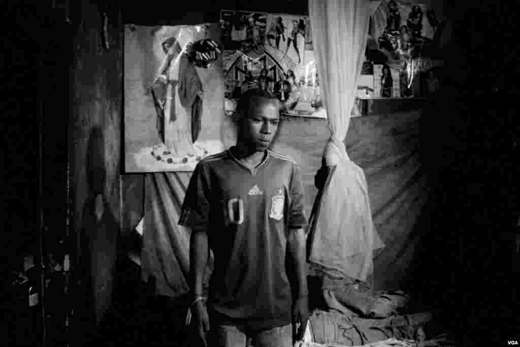 Kuitonda David, age 24, in his room at a billiards hall where he works. He takes turns, sleeping on the one bed in this room, with his work mate,Nzamwita Afrodis, who is HIV positive, Giporoso, Kigali, Rwanda, Nov. 27, 2013. (Hamada Elrasam for VOA)