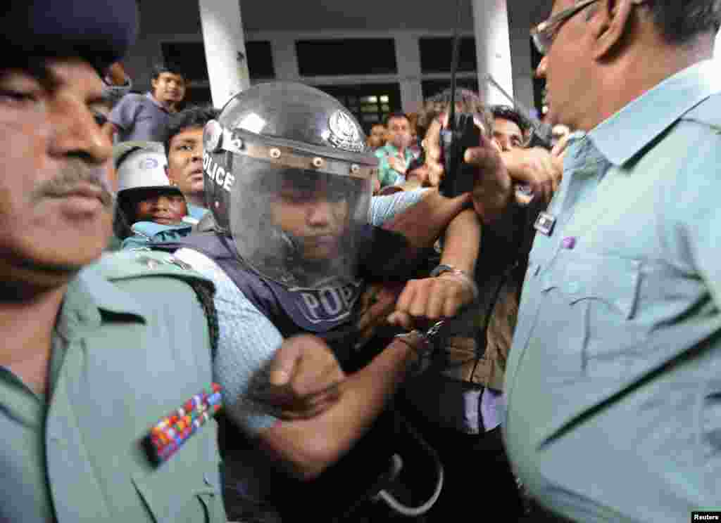 Members of the police escort the owner of the collapsed building, Mohammed Sohel Rana, in a police helmet for protection after his hearing at the High Court in Dhaka, Bangladesh, April 30, 2013.