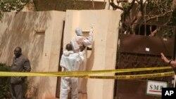 Les enquêteurs, centre, recueillent des preuves dans une discothèque qui a été attaquée par des hommes armés pendant que les forces armées assurent la sécurité à Bamako, au Mali, samedi 7 Mars, 2015.