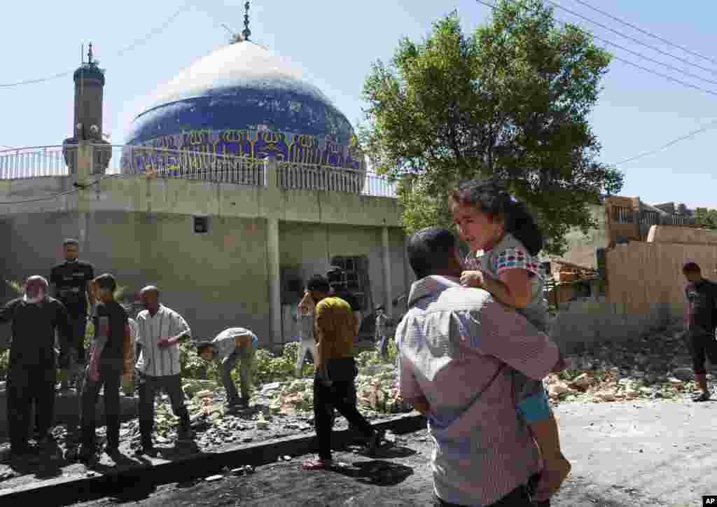 People clean up after a car bomb attack hit a Shi'ite mosque in Bayaa, Baghdad, July 29, 2013.