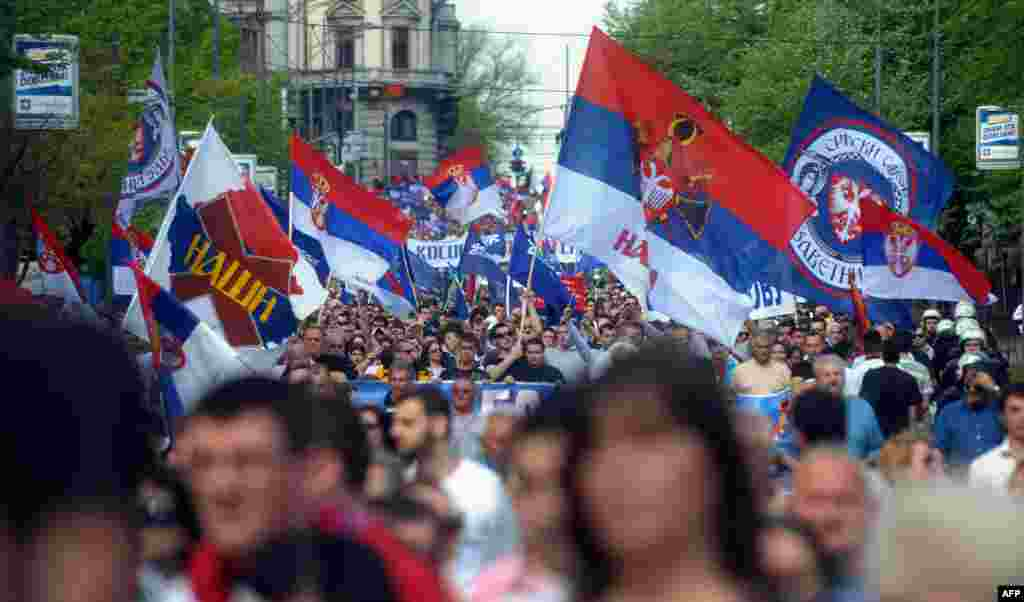 People wave flags as they a protest against an EU-sponsored deal to normalize ties between Serbia and breakaway Kosovo, in Belgrade, after the two governments approved the deal, a historic agreement aimed at turning the page on the Balkans' last simmering trouble-spot 14 years after the end of hostilities.