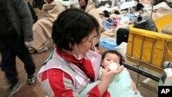 日本的红十字会工作人员在救援中心为婴儿喂奶