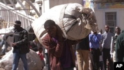 FILE: A vendor carries his goods after he was evicted from the streets by Zimbabwean police in Harare, Wednesday, July, 8, 2015. (AP Photo/Tsvangirayi Mukwazhi)