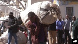 A vendor carries his goods after he was evicted from the streets by Zimbabwean police in Harare, Wednesday, July, 8, 2015. (AP Photo/Tsvangirayi Mukwazhi)
