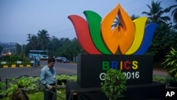 An Indian policeman from bomb squad checks a roundabout with a huge BRICS logo, in Goa, Oct. 14, 2016.