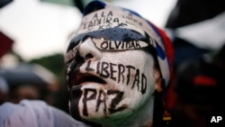 "A woman with her face painted with Spanish words for; ""Freedom, peace, don't forget,"" attends a vigil to honor the more than 90 people killed during three months of anti-government protests in Caracas, Venezuela, July 13, 2017."