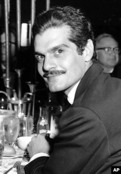 """FILE - Actor Omar Sharif poses for a photo at a dinner party following the movie premiere of """"Lawrence of Arabia"""" in Hollywood, California, Dec. 21, 1962."""