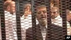 埃及內政部提供的視頻顯示被推翻的總統穆爾西在羈押被告的囚籠內講話。(2013年11月3日)