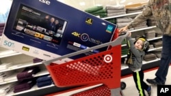 FILE - Hunter Harvey and his dad, C.J., plan to purchase a big screen TV at Target, in Wilmington, Massachusetts, Nov. 25, 2016. The U.S. Commerce Department reported Tuesday, Nov. 29, 2016, that the economy grew faster than expected between July and September due to strong consumer spending.