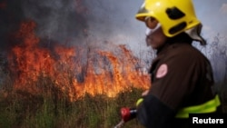 A firefighter monitors a spot fire in an area of the Amazon rainforest, near Porto Velho, Rondonia State, Brazil August 16, 2020. (REUTERS/Ueslei Marcelino)