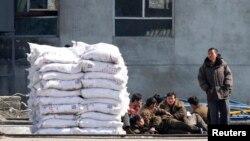 지난 3월 중국 단둥과 북한 신의주를 오가며 일하는 북한 노동자들이 비료 더미 옆에 앉아있다.
