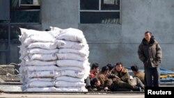 지난해 3월 북-중 국경 지역인 단둥에서 바라본 북한 신의주. 비료 더미가 쌓여있는 옆으로 북한 인부들이 앉아있다. (자료사진)