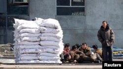 지난해 3월 중국 단둥에서 압록강 넘어로 바라본 북한 신의주에 비료 더미가 쌓여있다. (자료사진)