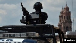 FILE - A Federal police patrol mans a weapon atop a vehicle in Morelia, in the Mexican state of Michoacan Oct. 28, 2013. Mexico stepped up security in the troubled western region after a string of attacks on electricity installations temporarily knocked out power for hundreds of thousands of people.