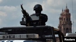 FILE - Federal police patrol mans a weapon atop a vehicle in Morelia, in the Mexican state of Michoacan Oct. 28, 2013.