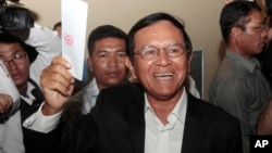 Opposition Cambodia National Rescue Party President Kem Sokha shows off his ballot before voting in local elections in Chak Angre Leu on the outskirts of Phnom Penh, Cambodia, Sunday, June 4, 2017. (AP Photo/Heng Sinith)