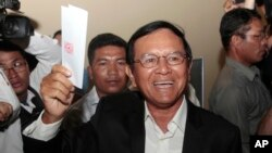 Opposition Cambodia National Rescue Party President Kem Sokha shows off his ballot before voting in local elections in Chak Angre Leu on the outskirts of Phnom Penh, Cambodia, Sunday, June 4, 2017. Cambodians are voting in local elections that could shake longtime ruler Hun Sen's grip on power. (AP Photo/Heng Sinith)