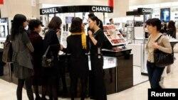 顾客在韩国首尔新世界百货商店化妆品柜台前挑选物品。(资料照)
