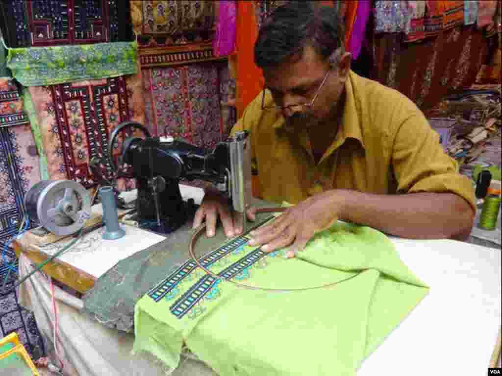 کراچی کی لیمارکیٹ میں ایک کاریگر بلوچی روایتی لباس پر مشین سے کڑھائی کرتے ہوئے
